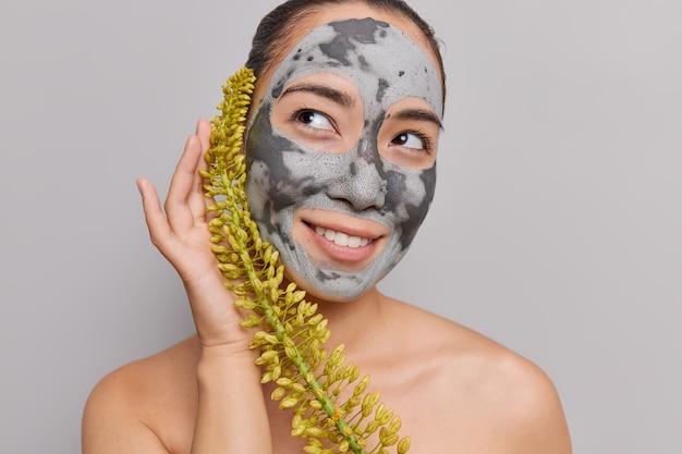 Frau hat minimales make-up trägt tonmaske auf, sieht weg mit verträumtem ausdruck verwendet pflanzliches naturkosmetikprodukt steht nackt isoliert auf grau