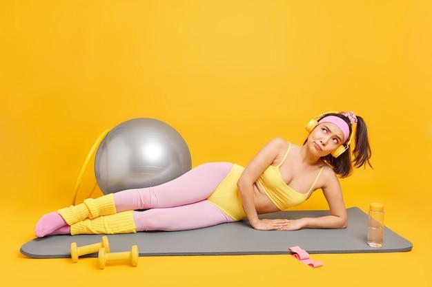 Frau hat nachdenklichen ausdruck liegt auf fitnessmatte geht zum sport macht aerobic-übungen hört musik über kopfhörer in activewear isoliert auf gelb