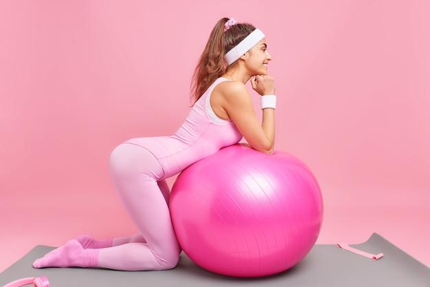 Frau hat perfekte figur macht pilates-übungen mit schweizer ball hält fit posen auf knien auf fitnessmatte in aktivkleidung