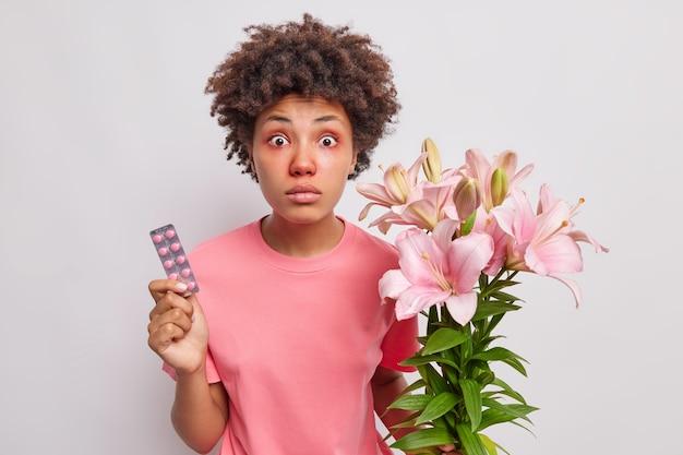 Frau hat pollenallergie-krankheit hält pillen und blumenstrauß von lilien hat allergische reaktion auf saisonblumen hat rote augen und nase über weiß isoliert