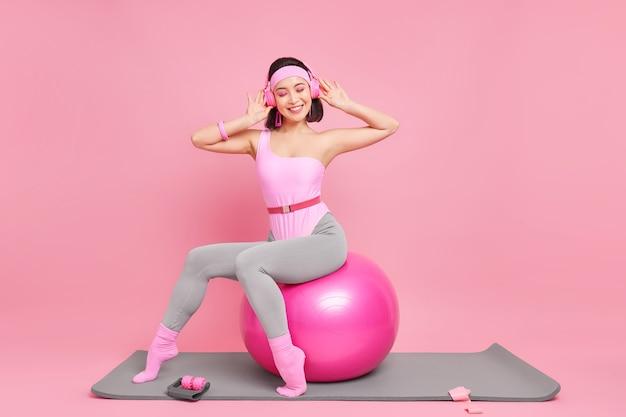 Frau hat schlanke figur macht yoga-übungen mit fissball in sportkleidung gekleidet posiert auf fitnessmatte hört musik über kopfhörer