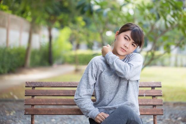 Frau hat schulterschmerzen im park