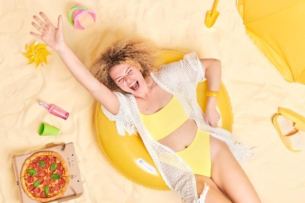 Frau hat spaß am strand liegt am schwimmen im gelben bikini gekleidet hebt arm genießt urlaub umgeben von strandaccessoires posiert auf weißem sand.