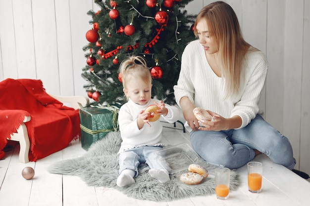 Frau hat spaß, sich auf weihnachten vorzubereiten. mutter im weißen pullover spielt mit tochter. die familie ruht sich in einem festlichen raum aus.