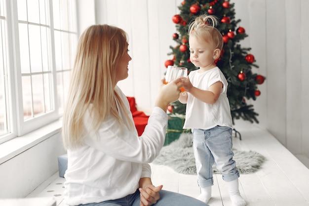 Frau hat spaß, sich auf weihnachten vorzubereiten. mutter in einem weißen hemd spielt mit ihrer tochter. die familie ruht sich in einem festlichen raum aus.