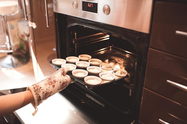 Frau hat teig für cupcakes in den ofen gestellt