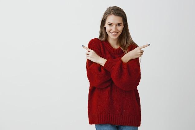 Frau hat überraschung und bittet, richtung zu wählen. innenaufnahme der gut aussehenden europäischen frau im stilvollen losen roten pullover, der auf beiden seiten mit zeigefingern zeigt und breit über graue wand lächelt