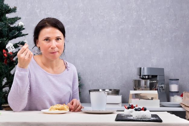 Frau hausfrau isst dessert in der küche. porträt der frau, die tee trinkt.