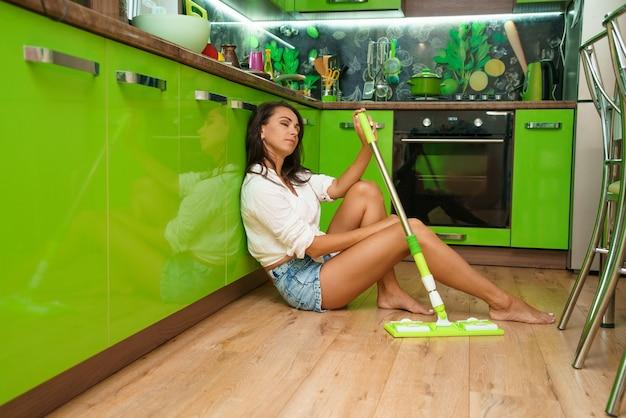 Frau hausfrau mit mopp den boden in der küche reinigen
