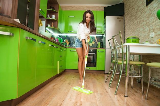 Frau hausfrau mit mopp reinigung des bodens in der küche regelmäßige hausreinigung kaukasisches mädchen war...