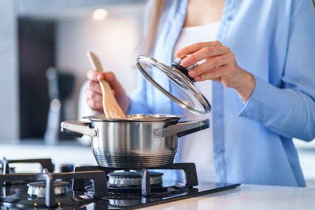 Frau hausfrau mit stahl metallic topf für die zubereitung des abendessens in der küche zu hause. küchenutensilien zum kochen