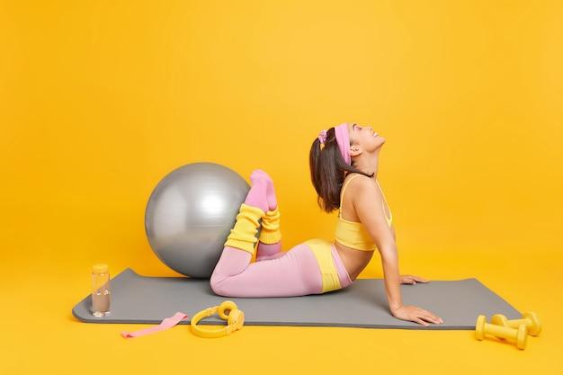 Frau hebt beine zeigt ihre flexibilität trägt abgeschnittenes oberteil und leggings posiert auf fitnessmatte macht übungen mit schweizer ball fühlt sich glücklich isoliert auf gelb