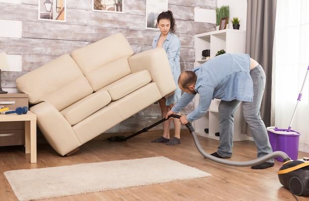 Frau hebt das sofa hoch, während ihr mann den staub darunter mit dem staubsauger säubert
