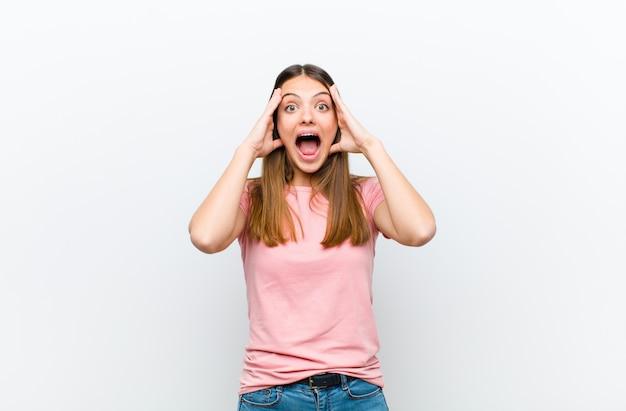 Frau hebt die hände zum kopf, mit offenem mund, fühlt sich sehr glücklich, überrascht, aufgeregt und glücklich