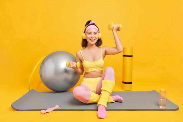 Frau hebt hanteln hört musik über kopfhörer trägt abgeschnittene top leggings stirnband hat sportliche figur führt aktive lifestyle-posen auf fitnessmatte auf gelb