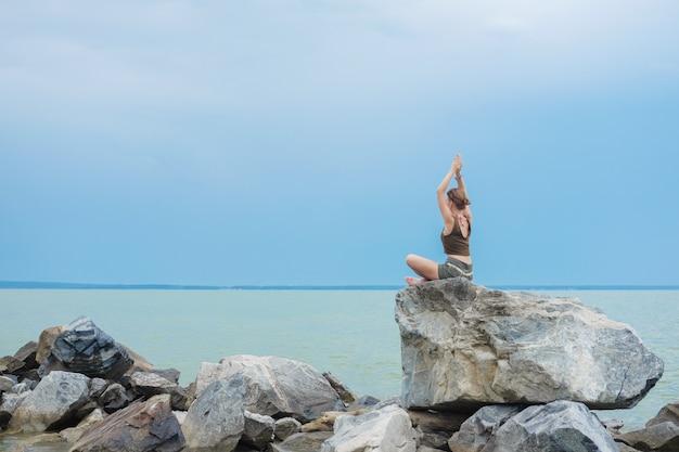 Frau hebt ihre arme in namaste-haltung zum himmel und sitzt in einer lotus-pose.