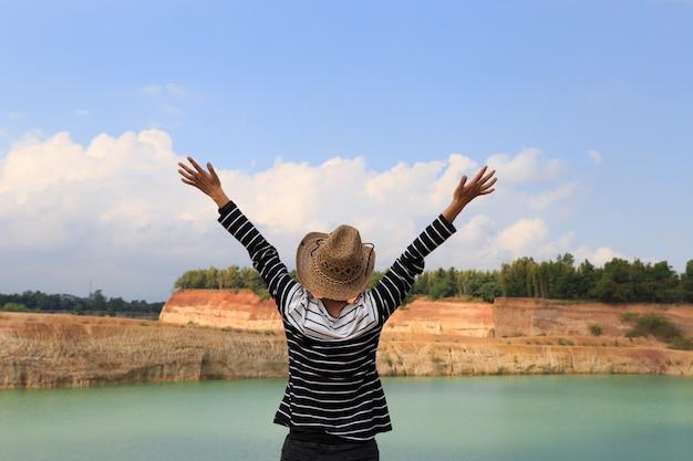 Frau hebt ihre hände hoch und fühlt sich glücklich und frei am orangefarbenen hügel und am grünen teich