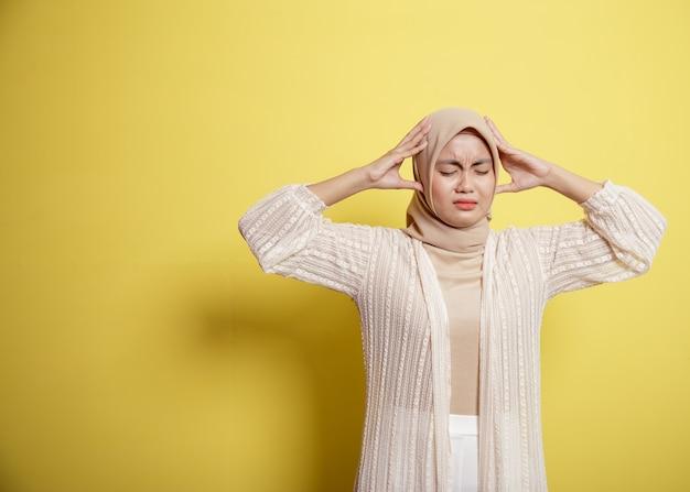 Frau hijab mit einem schwindelerregenden ausdruck, der etwas lokalisiert auf gelber wand denkt