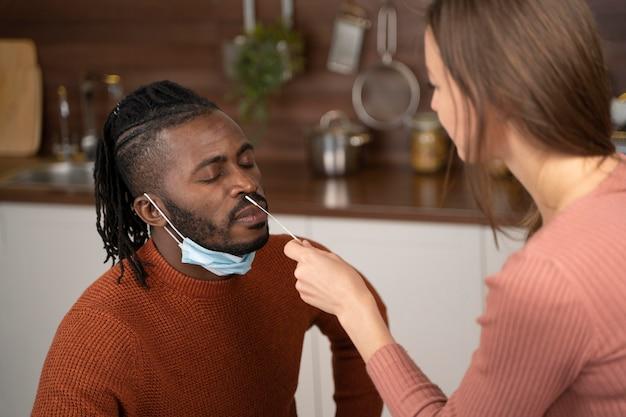Frau hilft ihrem mann bei einem covid-test zu hause