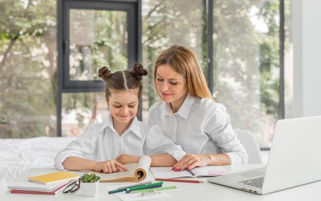 Frau hilft ihrem schüler mit ihren hausaufgaben