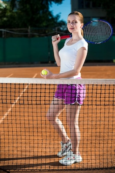 Frau hinter der tennisleiste, die den tennisball hält
