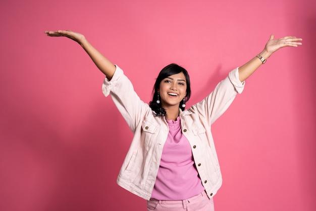 Frau hob arm glücklich auf rosa