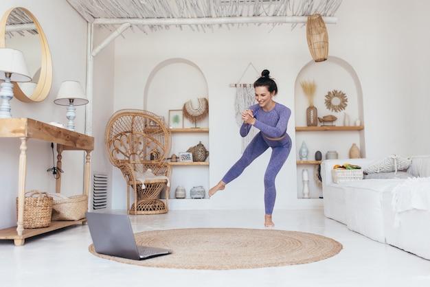 Frau hockt auf einem bein. online-schulung zu hause. online workout klasse.