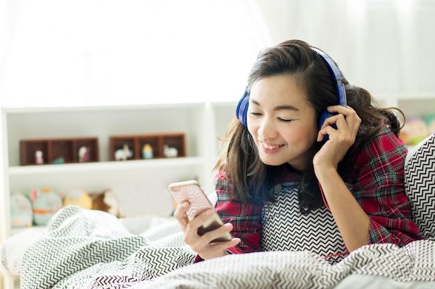 Frau hören musik und mit smartphone in ihrem schlafzimmer zum entspannen