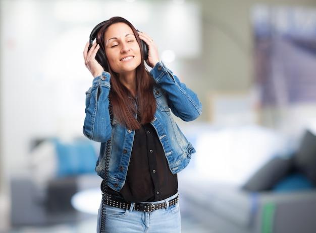 Frau hören von musik mit kopfhörern