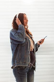 Frau hört angenehme klassische musik mit dem smartphone