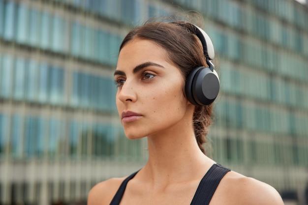 Frau hört audiospur in weiten kopfhörern wartet auf couch, um mit dem training zu beginnen denkt über wichtige frage nach, die auf distanz konzentriert ist, führt zu aktivem lebensstil