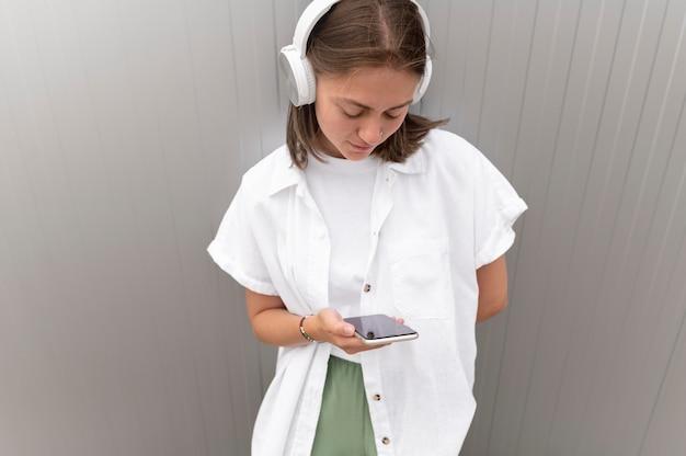 Frau hört musik über ihre kopfhörer, während sie ihr smartphone hält