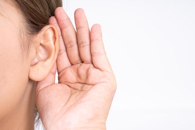 Frau hörverlust oder schwerhörig und hüllt ihre hand hinter ihr ohr.