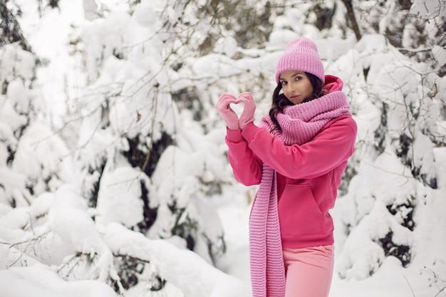 Frau ich machte ein herz mit meinen händen in rosa kleidern, einer jacke, einem gestrickten schal und einer mütze, die im winter in einem verschneiten wald steht