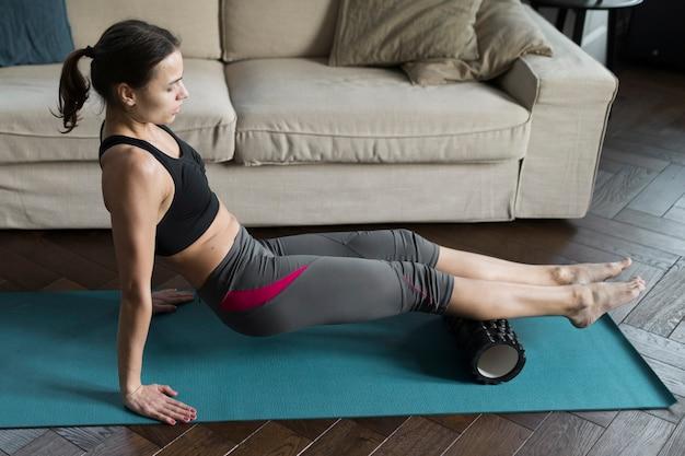 Frau im activewear, der zu hause übungen tut