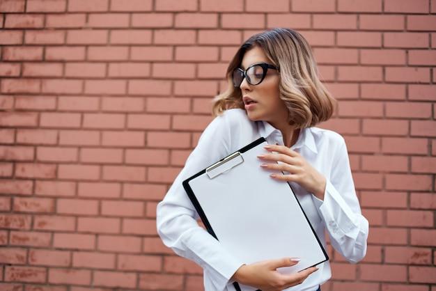 Frau im anzug brick wall ordner für papiere professioneller heller hintergrund. foto in hoher qualität