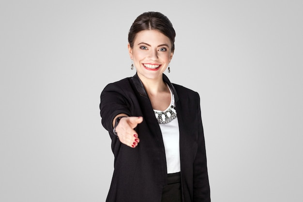 Frau im anzug, der kamera betrachtet und handshakezeichen zeigt. studioaufnahme, drinnen. auf grauem hintergrund isoliert