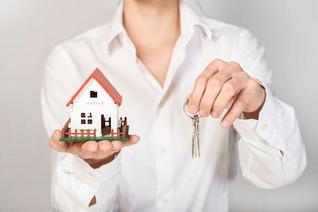 Frau im anzug, der spielzeugmusterhaus und -schlüssel hält