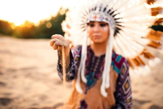 Frau im anzug des indianers auf sonnenuntergang