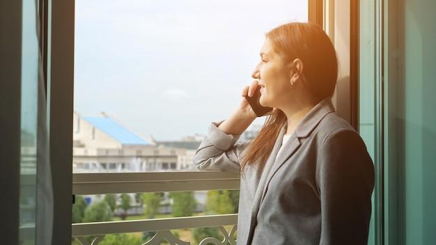 Frau im anzug, die an einem sonnigen tag am offenen fenster telefoniert.