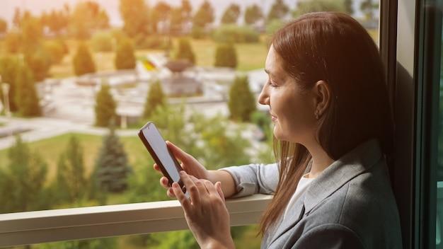 Frau im anzug telefoniert am offenen fenster