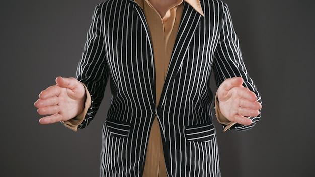 Frau im anzug zeigt größe mit den händen. hochwertiges foto