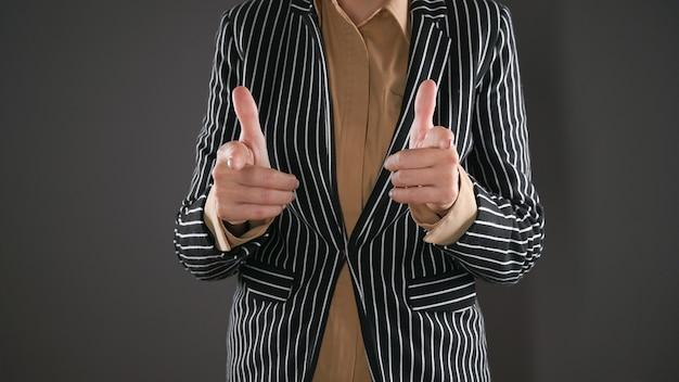 Frau im anzug zeigt mit dem zeigefinger nach vorne. hochwertiges foto