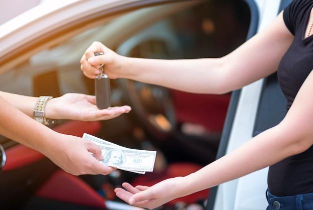 Frau im ausstellungsraum, der dollargeld gibt und schlüssel vom auto nimmt
