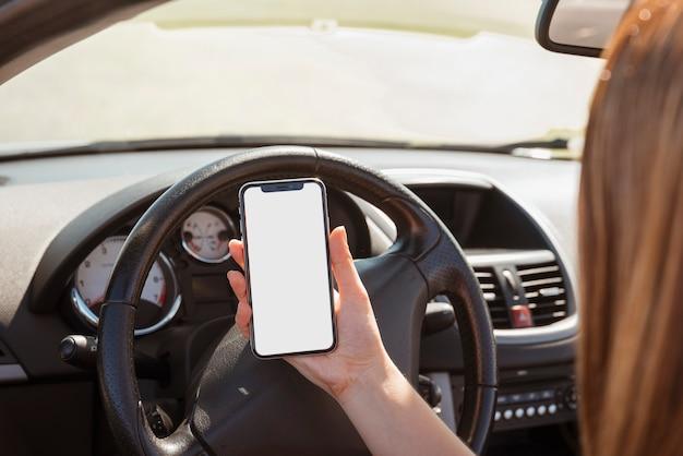 Frau im auto, das smartphoneschablone betrachtet