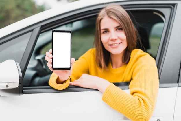 Frau im auto, das telefonschirm zeigt