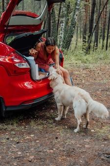 Frau im auto, die pizza mit goldenem apportierhund isst