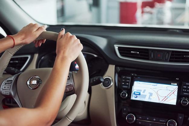 Frau im auto drinnen hält rad umdrehend lächelnd und betrachtet passagiere auf dem rücksitz idee taxifahrer gegen sonnenuntergangsstrahlen lichtscheinhimmel konzept der prüfung fahrzeug - zweites zuhause das mädchen
