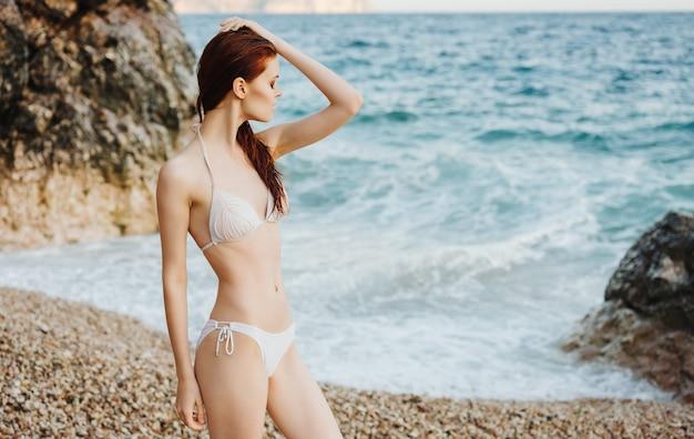 Frau im badeanzug auf den luxuriösen sommerferien der strandtropen