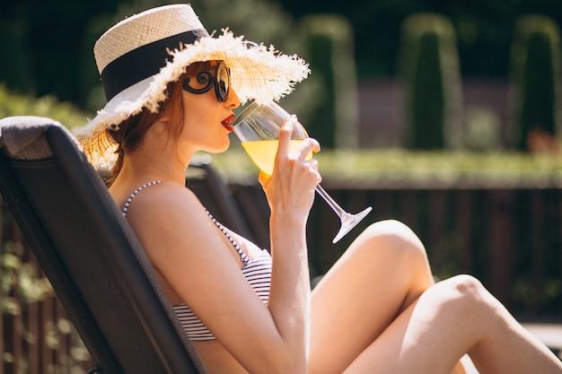 Frau im badeanzug auf einem trinkenden saft der ferien